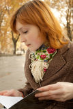 De lezingsboek van het meisje in de herfstpark Royalty-vrije Stock Foto