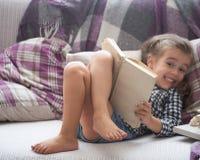 De lezingsboek van het meisje op bank Royalty-vrije Stock Foto's