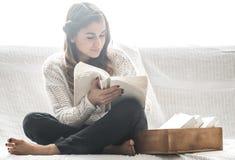 De lezingsboek van het meisje op bank Stock Foto's