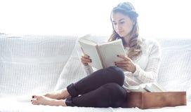 De lezingsboek van het meisje op bank Stock Afbeeldingen