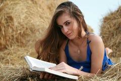 De lezingsboek van het meisje op hooiberg royalty-vrije stock afbeelding