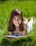 De lezingsboek van het meisje openlucht stock foto