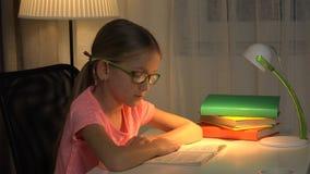 De lezingsboek van het oogglazenkind, meisje die bij bureaulamp bestuderen, lerende kinderen 4K stock video