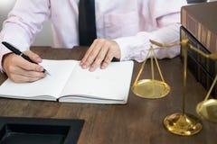 De lezingsdocumenten van de advocaatrechter bij bureau in rechtszaal die aan houten bureauachtergrond werken hamer gouden Gewicht stock afbeelding