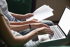 De de lezingsdocumenten van de paarholding thuis met laptop, sluiten omhoog stock foto