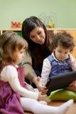 De lezingssprookje van de leraar aan kinderen op school stock afbeelding