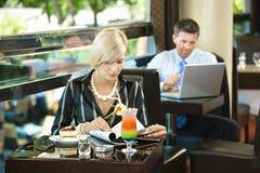 De lezingstijdschrift van de vrouw in koffie stock afbeelding