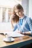 De lezingstijdschrift van de vrouw in koffie Royalty-vrije Stock Foto's
