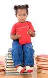 De lezingszitting van de baby op een stapel van boeken Royalty-vrije Stock Afbeeldingen