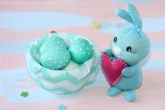De lichtblauwe konijntje genaaide handen van Pasen met een hart in zijn poten dichtbij de stoffenmand met blauw-witte eieren Groe stock foto