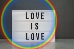 De lichte doos met `-liefde is liefde ` en regenboog Stock Foto's