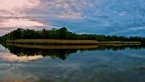 De lichte onweerswolken bewegen zich over een wilde gebieds Levendige zonsondergang bij watermeer, met dramatische wolkenbeweging stock video