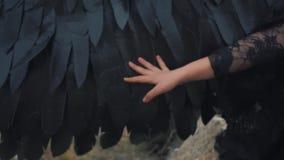 De lichte tedere hand houdt een zwarte sterke vleugel overhandig, zit de dochter van een engel en een demon op stock videobeelden
