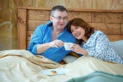 De lichte theekop met een hete drank De echtgenoot bracht zijn koffie van de vrouwenthee aan het bed stock afbeelding