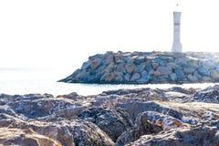 De lichte toren van de steigerpijler, natuurlijke mooie rots en overzees met zonneschijnbezinning royalty-vrije stock foto's
