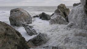 De lichte wind blaast - omhoog overzees-schuim op de rotsachtige kust in bewolkt weer 4K stock video