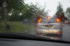 De lichten van de autostaart door een regen behandelden windscherm, nadruk op regendalingen Royalty-vrije Stock Afbeeldingen