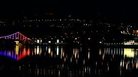 De lichten van de nachtstad over de rivier stock video