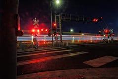 De lichten van een forenzentrein gaan wegschietend door een straatscène aangezien de nacht valt royalty-vrije stock fotografie