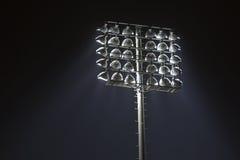 De lichten van het stadion tegen de donkere achtergrond van de nachthemel Stock Afbeelding