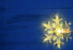 De lichten van de Kerstmisslinger LEIDENE sneeuwvlok gevormde bol op blauwe houten achtergrond Royalty-vrije Stock Foto