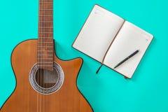 De liedschrijver dient een werkruimte met musicus akoestisch gitaar en blocnotedocument in stock foto