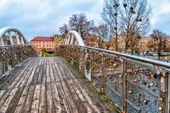De liefdebrug in Bydgoszcz, Polen, het hangslotliefjes van het Liefdeslot sloot over, oude rijtjeshuizen met voetgangersbrug, bru Stock Fotografie