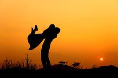 De liefdesilhouet van de man en van de Vrouw in zonsondergang Stock Foto