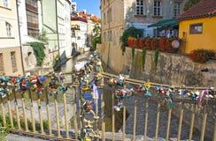 De liefdesloten hangen van een brug over de rivier Certovka in Praag Stock Afbeelding