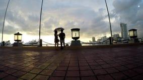 De liefjes die bij kustbaai dateren lopen in paraplu Silhouetten stock videobeelden