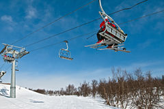 De lift van de stoel met skiërs op een blauwe hemel Stock Foto
