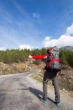 De liftende reiziger probeert om auto op de bergweg tegen te houden Stock Afbeeldingen