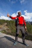 De liftende reiziger probeert om auto op de bergweg tegen te houden Royalty-vrije Stock Foto's