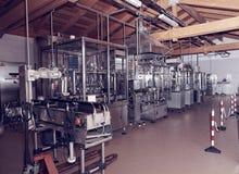 De lijn van het bottelen van wijnmateriaal in een gestemde hangaar, Royalty-vrije Stock Foto's