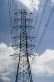De lijnen en de pyloon van de elektriciteitstransmissie tegen blauwe hemel en wolk, hoogspanningstoren worden gesilhouetteerd die Stock Afbeelding