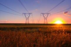 De lijnen van de elektriciteitsmacht met zon bij schemer Royalty-vrije Stock Afbeelding