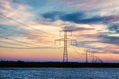 De lijnen van de hoogspanningselektriciteit over rivier bij zonsondergang Stock Afbeelding
