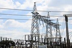 De lijnen van de hoogspanningsmacht met elektriciteitspylonen bij blauwe hemel stock foto's