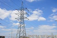 De lijnen van de hoogspanningsmacht met elektriciteitspylonen bij blauwe hemel stock afbeelding
