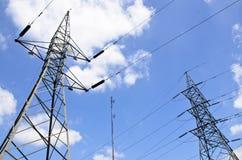 De lijnen van de hoogspanningsmacht met elektriciteitspylonen bij blauwe hemel royalty-vrije stock afbeeldingen