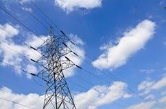 De lijnen van de hoogspanningsmacht met elektriciteitspylonen bij blauwe hemel stock afbeeldingen