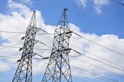 De lijnen van de hoogspanningsmacht met elektriciteitspylonen bij blauwe hemel stock fotografie