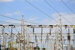De lijnen van de hoogspanningsmacht met elektriciteitspylonen bij blauwe hemel stock foto