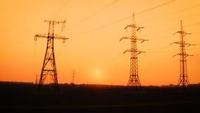 De lijnen van de hoogspanningsmacht bij het gebied in zonsondergangtijd stock footage