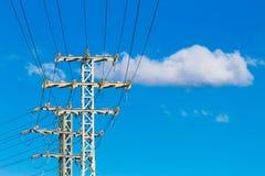 De lijnen van de hoogspanningsmacht en elektrische transmissiepyloon met blauwe hemelachtergrond Stock Foto's