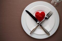 De lijst die van de valentijnskaartendag met rood hart en bestek op een plaat plaatsen Stock Afbeelding
