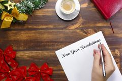 De lijst die van nieuwjaarresoluties op houten raad liggen Mens die doellijst maken stock afbeelding