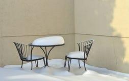 De Lijst en de Stoelen van het Terras van het ijzer die met sneeuw wordt behandeld. Stock Afbeeldingen