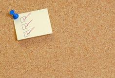 De lijst van de controle die op corkboard wordt gepost stock fotografie