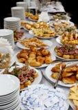 De lijst van het cateringsbanket met gebakken voedselsnacks, sandwiches, cakes, koppen en platen Stock Foto's